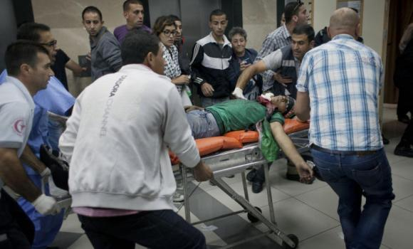 An injured Palestinian protester is moved to the emergency room at Ramallah Hospital, in the West Bank city of Ramallah, late Thursday. Violence spread to the West Bank, where thousands of Palestinians protesting the Gaza fighting clashed with Israeli soldiers late Thursday in Qalandia, near Ramallah.