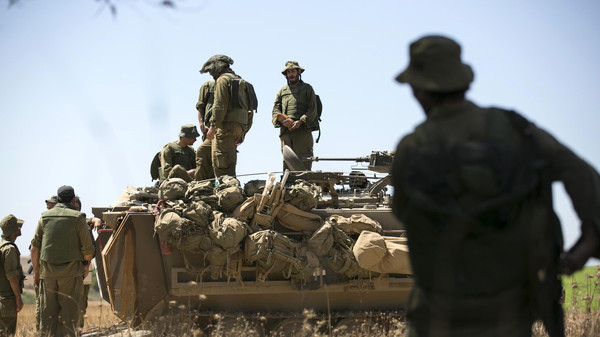 Israeli army reservists stand atop an armored personnel carrier (APC) outside the central Gaza Strip July 16, 2014.