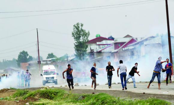Kashmiris throw stones at Indian policemen after a deadly accident in Srinagar on Wednesday.