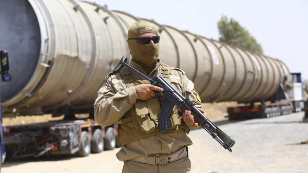 A member of the Kurdish security forces takes up position with his weapon as he guards a section of an oil refinery, which is being brought on a truck to Kalak refinery in the outskirts of Arbil.