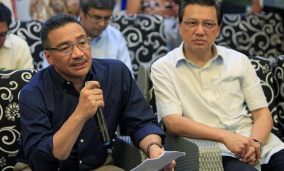 Malaysian Defense Minister Hishammuddin Hussein speaks as Malaysian Transport Minister Liow Tiong Lai listens during a press conference after the opening of the MH370 Tribute Photo Exhibition in Kuala Lumpur.
