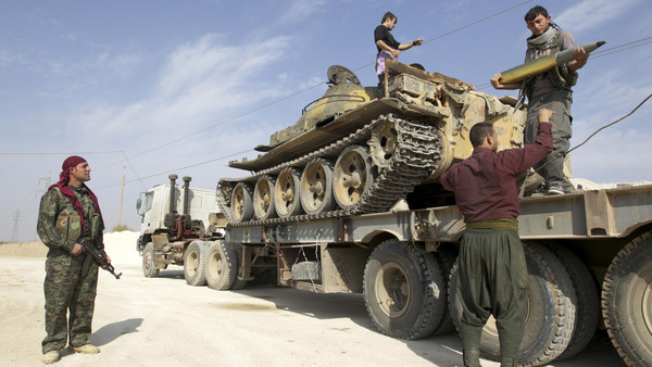 Members of Kurdish People's Protection Units (YPG) are seen on a military truck that belonged to the Islamist rebels after capturing it near Ras al-Ain, in the province of Hasakah.