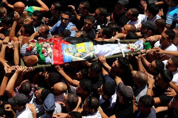 Mohamed Al Araj is carried through the Qalandia refugee camp near Ramallah