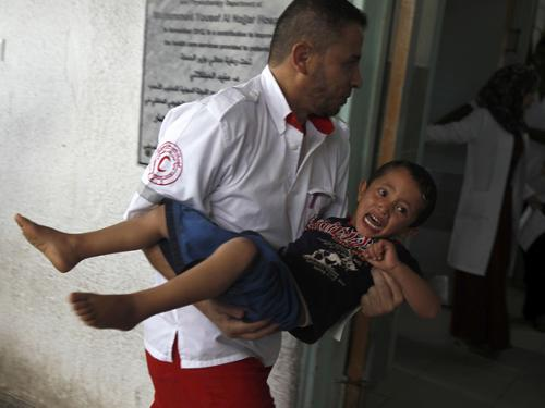 A member of the Palestinian Red Crescent Society carries an injured child at an hospital in Rafah, in the southern Gaza Strip, following an Israeli air strike before a five-hour truce went into effect on Thursday.