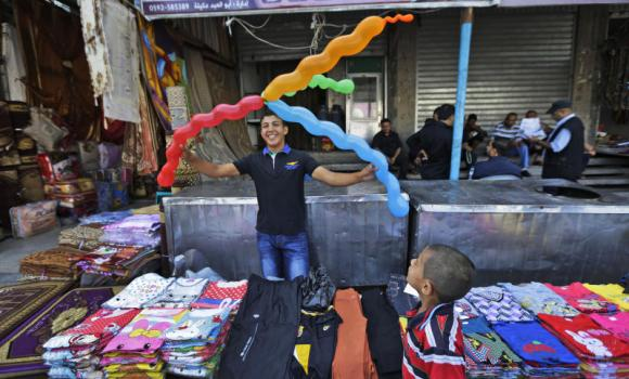 A Palestinian vendor plays with balloons at the market in the Jebaliya refugee camp, northern Gaza Strip, on Sunday, as Israel and the Hamas movement agreed to another round of ceasefire.