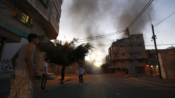 Palestinians stand looking at smoke billowing from a nearby building hit by an Israeli air strike in Gaza City on July 13, 2014.