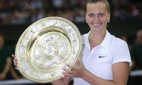 Petra Kvitova of Czech Republic holds the championship trophy following her victory over Eugenie Bouchard of Canada in the women's singles final of the Wimbledon Championships at the All England Lawn Tennis Club, in London, Britain, on Saturday.