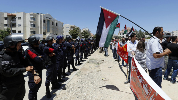 Police officers stand guard during a protest calling for an end to the Israeli air strikes in the Gaza Strip, near the Israeli embassy in Amman July 11, 2014.