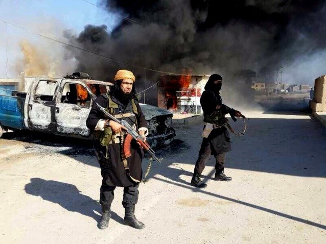 Shakir Waheib, a senior member of the al-Qaida breakaway group Islamic State of Iraq and the Levant (ISIL), left, next to a burning police vehicle in Iraq's Anbar Province