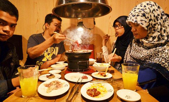In this June 24, 2014 photo shows Thai Muslim tourists enjoying Halal certified foods at a barbecue restaurant in Tokyo.