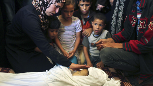 The mother of three-year-old Palestinian girl Jud al-Danaf touches her body during her funeral in Gaza City June 25, 2014.