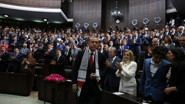 Turkey's Prime Minister Tayyip Erdogan leaves his seat to address members of parliament from his ruling AK Party (AKP) during a meeting at the Turkish parliament in Ankara July 22, 2014.