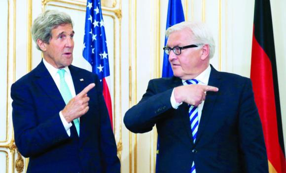 US Secretary of State John Kerry, left, and German Foreign Minister Frank-Walter Steinmeier gesture prior to a bilateral meeting, in Vienna, on Sunday.