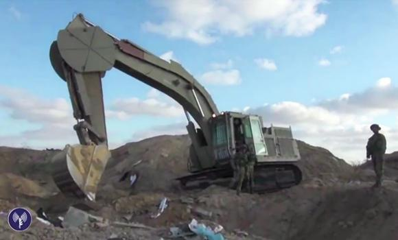 An Israeli military backhoe demolishes supposed tunnels built by the Hamas in this still image taken from a video distributed by the Israeli Defense Force through Agence France Presse.