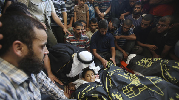 People surround the bodies of four-year-old Palestinian girl Sarah Sheik al-Eid, her father and her uncle, who medics said were killed in an Israeli air strike.