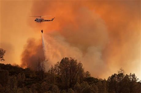 A Cal Fire helicopter makes a drop on the Butts Canyon Fire on Tuesday, July 1, 2014, near Middletown, Calif., close to the border between Lake and Napa counties. By early evening 140 homes were evacuated and 2,500 acres were burned.