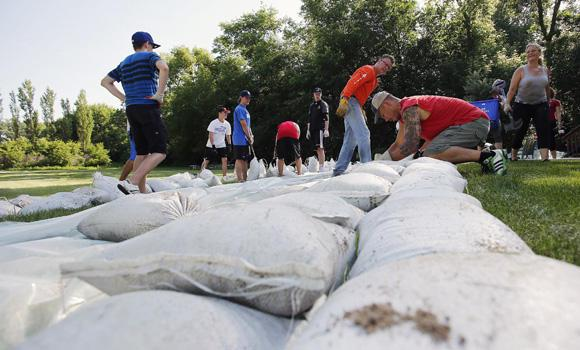 Friends and family build a sandbag dike in St Francois Xavier, Manitoba, on July 5, 2014. Tropical storm Arthur hit Canada's Maritime provinces with near-hurricane strength winds and torrential rains, knocking out power to nearly 200,000 customers.