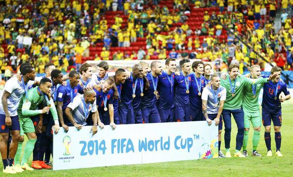 The Netherlands team poses for pictures after winning their 2014 World Cup third-place playoff against Brazil at the Brasilia national stadium in Brasilia on Saturday.