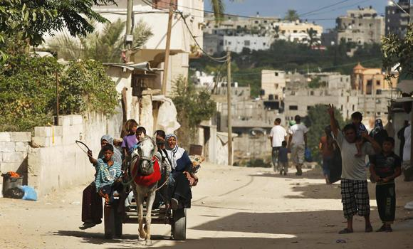 Palestinians, who fled their homes in the northern border town of Beit Lahiya, ride a horse cart as they make their way to stay at a United Nations-run school, in the northern Gaza Strip Monday. A UN aid agency said around a quarter of Beit Lahiya's 70,000 residents have fled.