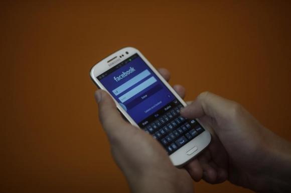 A smartphone user logs into his Facebook account in Rio de Janeiro.