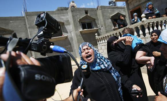 A Palestinian mourner cries as she talks to a TV journalist, while the bodies of Mousa Abu Muamer, 56, and his son Saddam, 27, who were killed in an overnight Israeli missile strike at their house are brought in during their funeral procession, on the outskirts of the town of Khan Younis, southern Gaza Strip, on Monday. Saddam's wife Hanadi, 27, was also killed in the attack.
