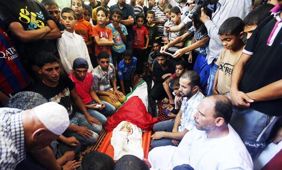 Palestinians surround the body of ten-year-old girl Nour al-Najdi, who hospital officials said was killed in an Israeli air strike, during her funeral at a mosque in Rafah in the southern Gaza Strip on Wednesday.