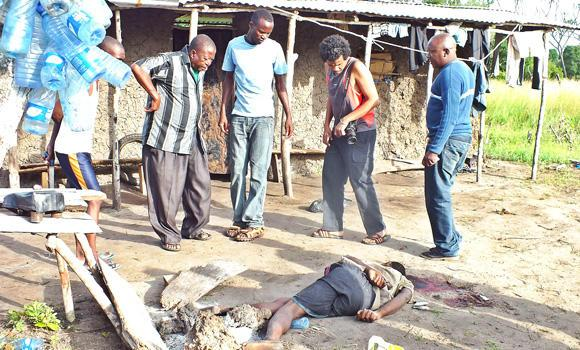 People gather around the body of a victim of a new attack in Kenya's coastal county of Lamu on Sunday.