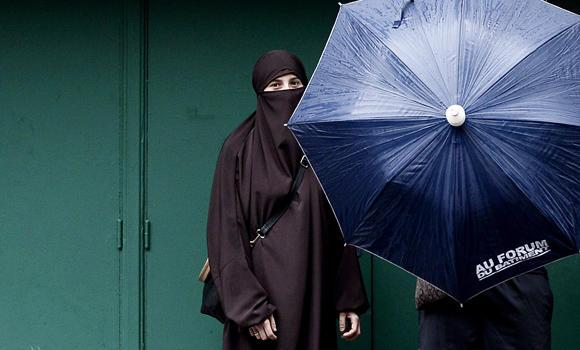 A woman wearing a niqab poses next to her husband (hidden by umbrella) in Paris on June 29, 2014. The European Court of Human Rights has upheld France's law banning face-covering veils from the streets.