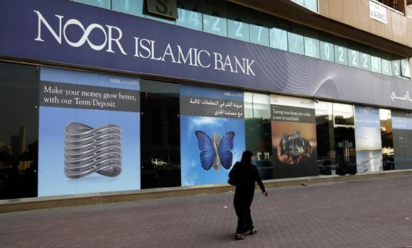 A woman walks past a branch of Noor Islamic Bank along Khalid Bin Al-Waleed Street in Dubai in this May 30, 2010 file photo. Islamic banking is based on core principles of the religion.