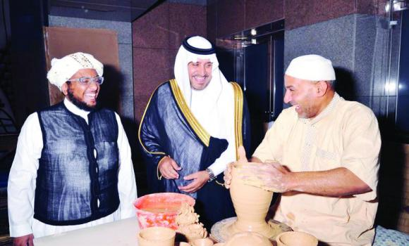 Mohammed bin Abdullah Al-Amri, the director of the Saudi Commission for Tourism and Antiquities, Makkah branch, has a light moment with a potter at the Forum and Exhibition for Handicrafts in Jeddah on Monday.