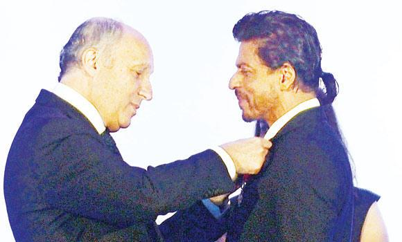 French Foreign Minister Laurent Fabius, left, awards Bollywood star Shah Rukh Khan with the Chevalier de la Legion d'Honneur title during a function in Mumbai on Tuesday.