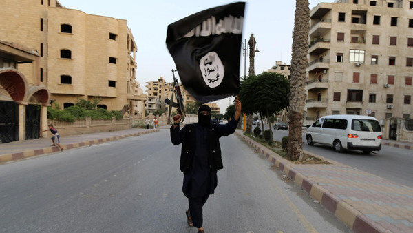 A member loyal to the Islamic State in Iraq and Syria (ISIS) waves an ISIS flag in Raqqa June 29, 2014.