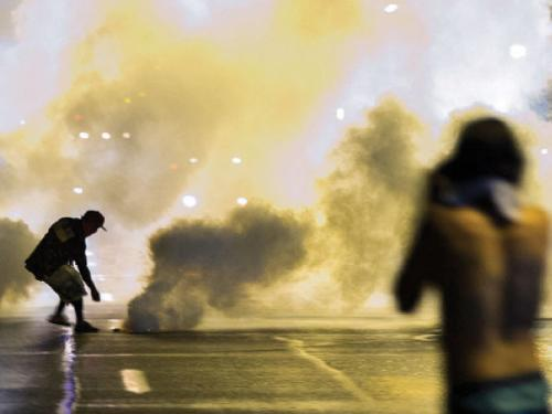 A protester reaches down to throw back a smoke canister as police clear a street after the passing of a midnight curfew meant to stem ongoing demonstrations in reaction to the shooting of Michael Brown in Ferguson, Missouri, on Sunday.