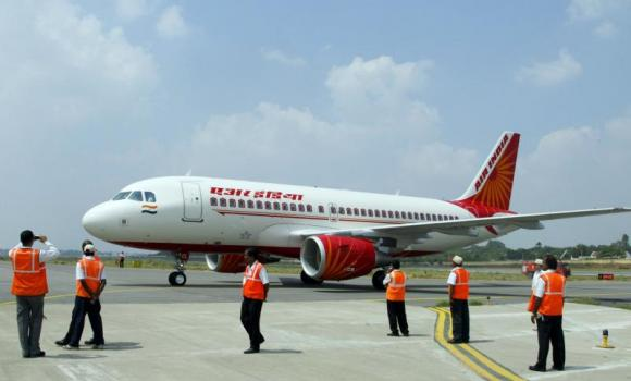 In this photograph taken on October 15, 2008, ground crew stand next to a newly-inducted Air India Airbus A319 aircraft during the opening day of India Aviation 2008 at Begumpet Airport in Hyderabad.