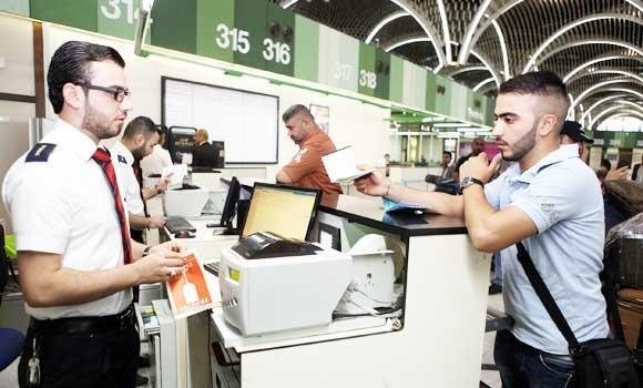 A passenger hands his passport for check-in at Baghdad International Airport, in this August 5, 2014 photo.
