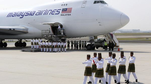 The remains of victims of the MH17 disaster are carried from a plane during a repatriation ceremony at the Bunga Raya complex of KLIA airport in Sepang.