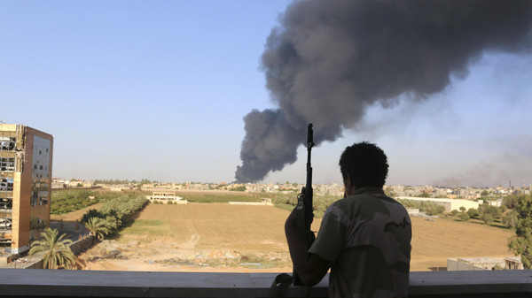 A fighter from Zintan brigade watches as smoke rises after rockets fired by one of Libya's militias struck and ignited a fuel tank in Tripoli August 2, 2014.