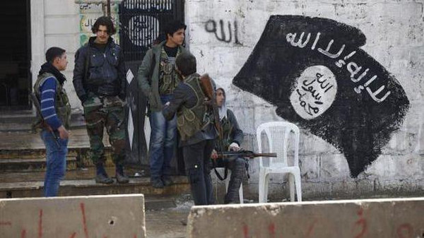 Free Syrian Army fighters stand at a former base used by fighters from the Islamic State in Iraq and Syria (ISIS), after ISIS withdrew from the town of Azaz, near the Syrian–Turkish border, on March 11, 2014.