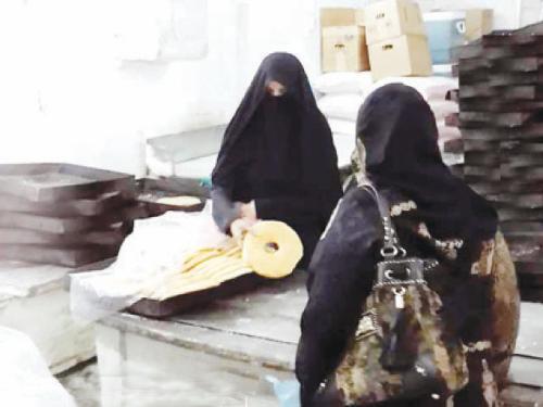 Hanan Naji serves a customer at Al-Saidi bakery in Souk Al-Alawi, downtown Jeddah.