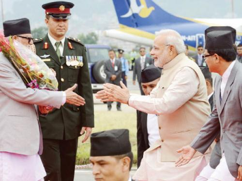Indian Prime Minister Narendra Modi (R) greets Nepalese Prime Minister Sushil Koirala on his arrival at Tribhuvan International Airport in Katmandu on Sunday.
