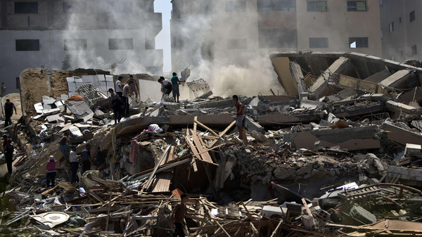 Palestinians look through the rubble of a 12-storey apartment building that collapsed, after it was hit by an Israeli air strike, the day before in Gaza City on August 24, 2014.