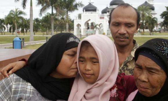 Jamaliah kisses her daughter Raudhatul Jannah, 14, as the girl's father Septi Rangkuti and grandmother Sarwani look on following prayers at Baiturrahman mosque in Banda Aceh.