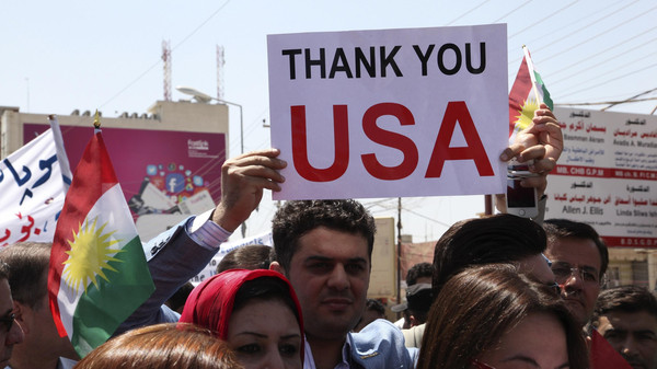 A Kurdish resident holds a signs during a demonstration in support of the Peshmerga troops in front of the U.S. consulate in Erbil, north of Baghdad, August 11, 2014.