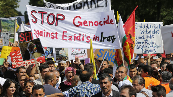 "Kurds of the ethnic minority of Yazidis hold up a banner reading ""Stop genocide against Yazidis in Iraq"" as they march through the streets of Bielefeld August 9, 2014."