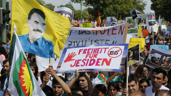 "Kurds of the ethnic minority of Yazidis wave a flag showing Abdullah Ocalan, the co-founder of the Kurdish Workers' party PKK, and a placard demanding ""Freedom for Yazidis."""