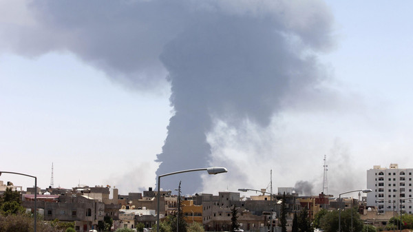 Smoke rises after rockets fired by one of Libya's militias struck and ignited a tank in Tripoli.