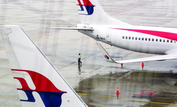 A Malaysia Airlines crew-member walks near their aircraft at Kuala Lumpur International Airport.