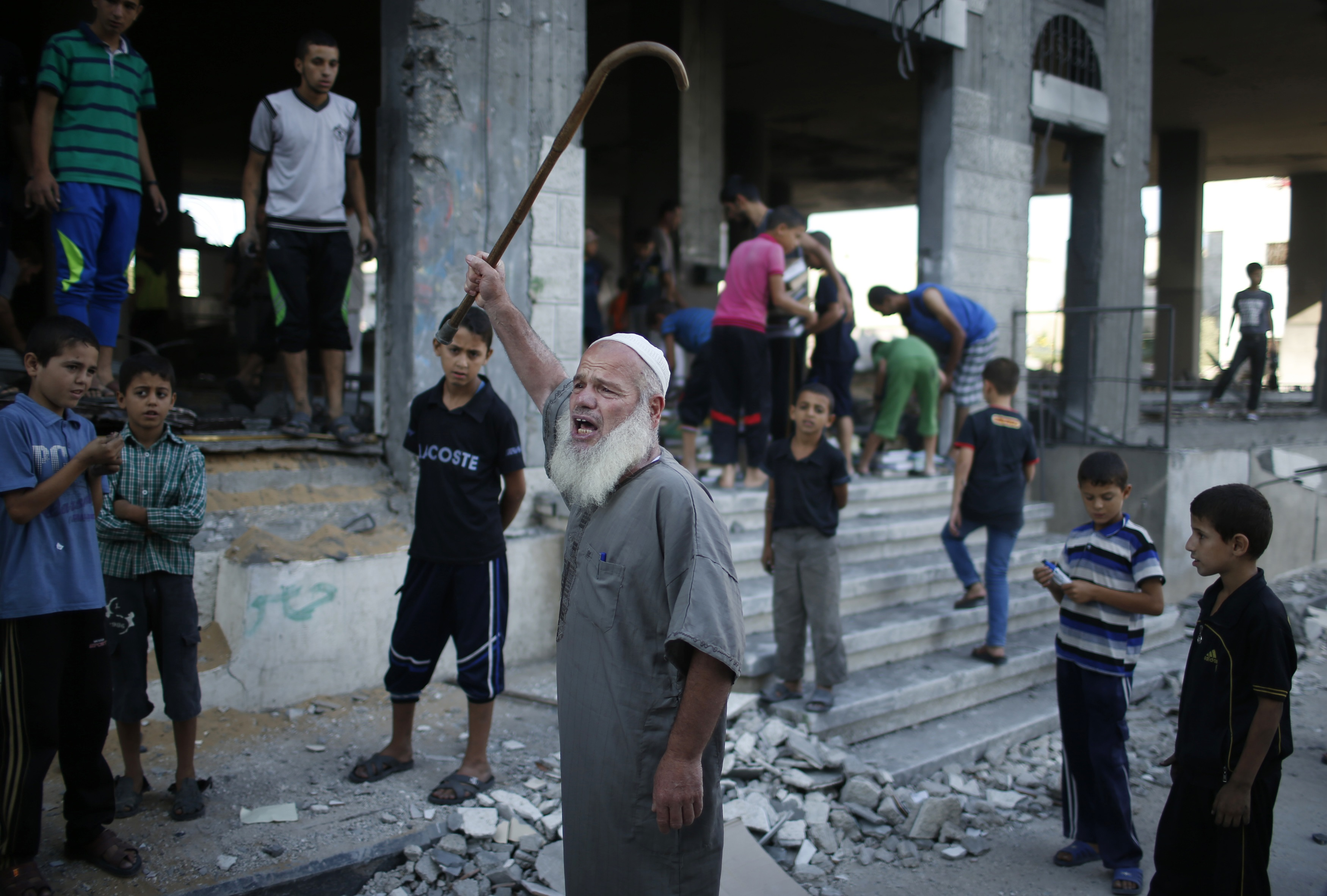 A Palestinian man reacts as he stands outside a badly damaged mosque, which witnesses said was hit in an Israeli air strike, in Gaza City August 9, 2014.
