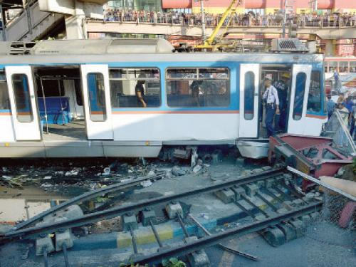 Rescue workers investigate at the scene after an overhead commuter train, center, overshot the last station, causing it to derail and smash through a wall in Manila on Wednesday.