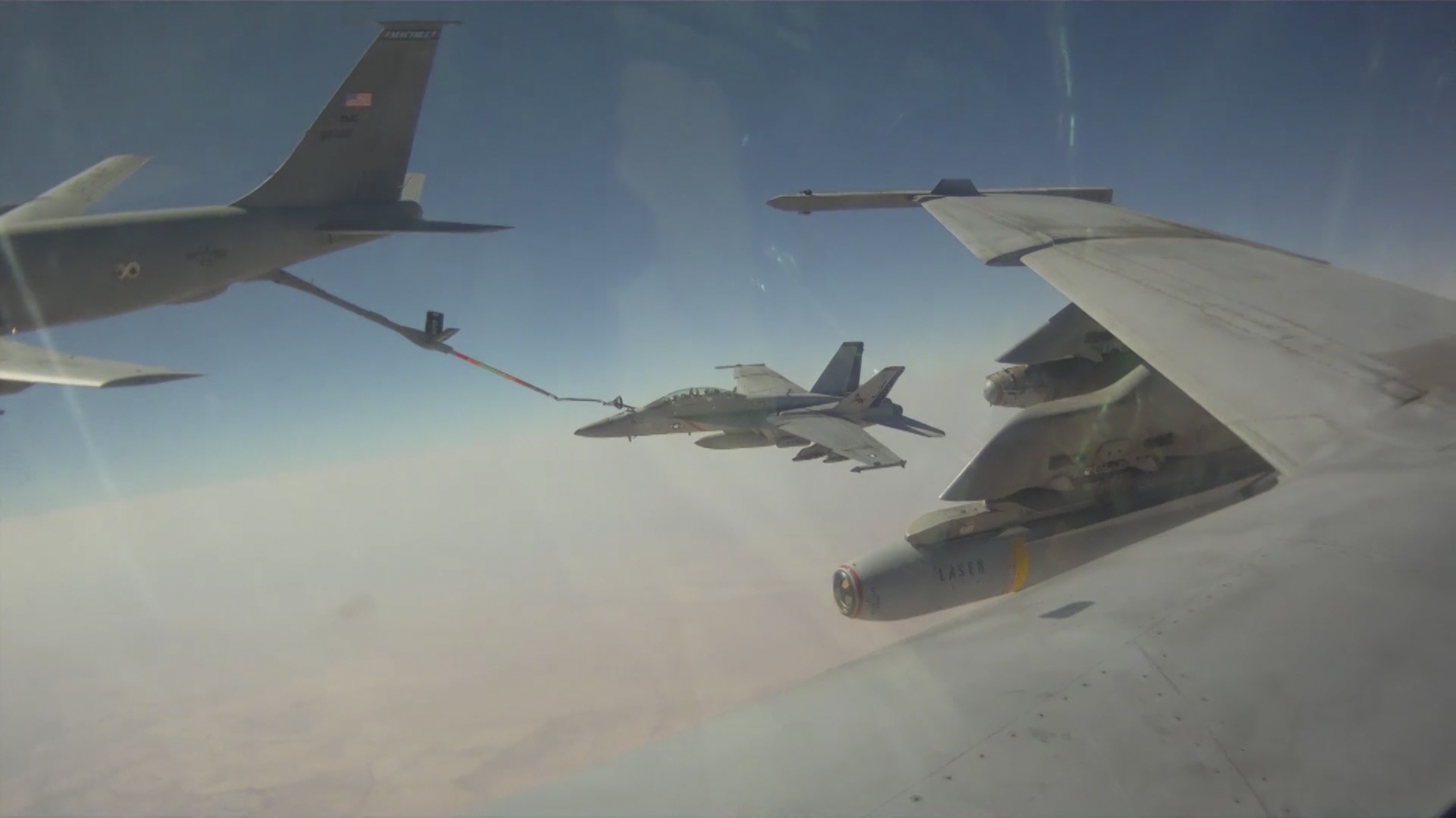 A still image captured from U.S. Navy cockpit video shows an F/A-18F Super Hornet assigned to the Fighting Black Lions of Strike Fighter Squadron (VFA) 213 in a mid-air refueling.